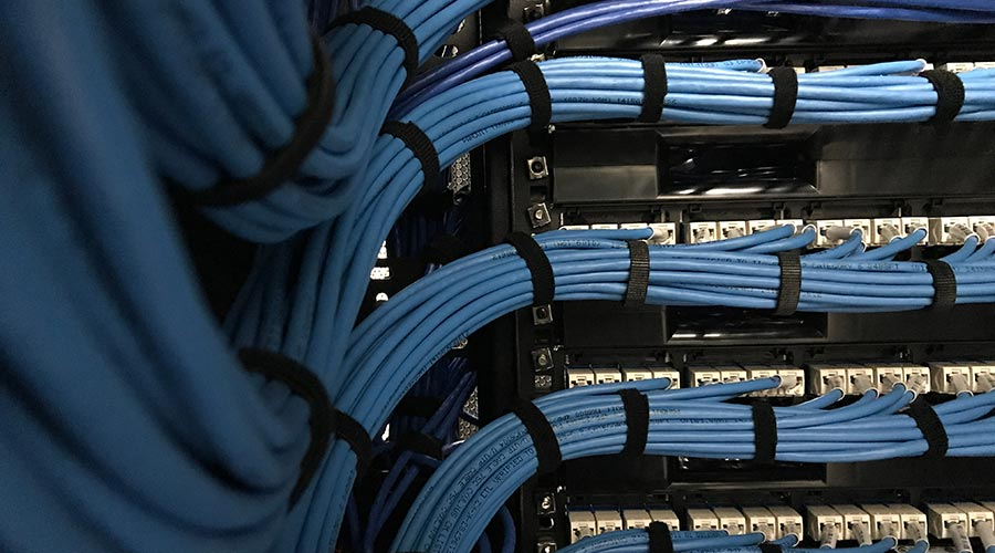 Large group of Ethernet cables in a rack cabinet of a in a server rack in the hybrid network data center room.